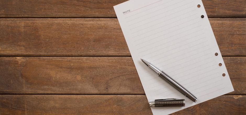 hoja de papel y bolígrafo sobre mesa de madera