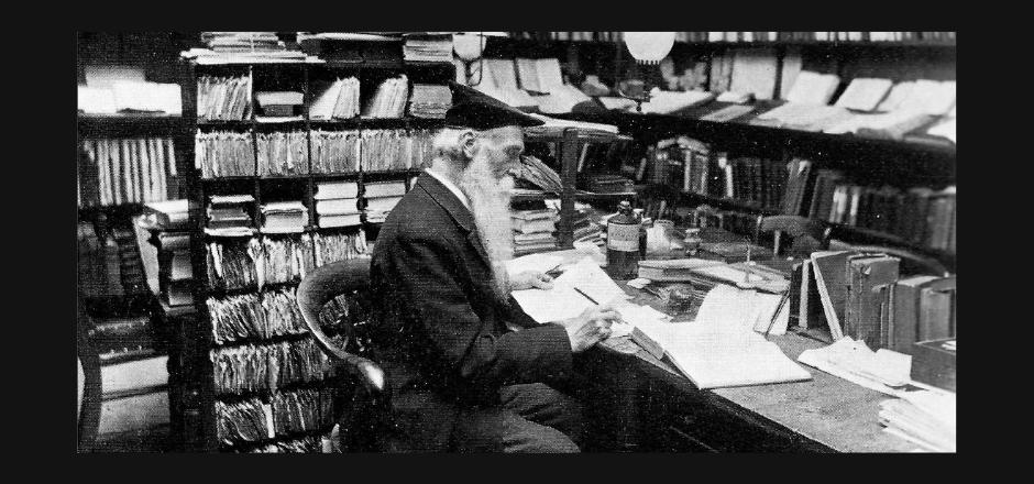 Foto en blanco y negro de un anciano leyendo rodeado de libros en una biblioteca