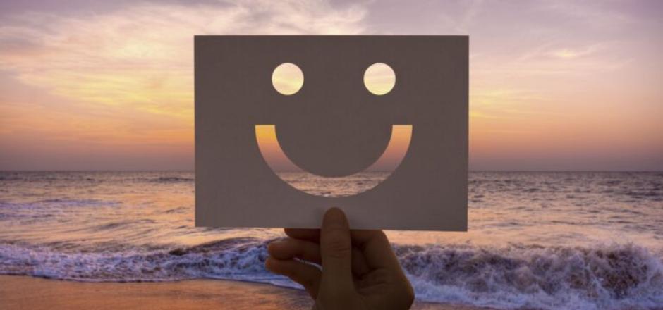 mano sosteniendo cara sonriente hecha de cartón