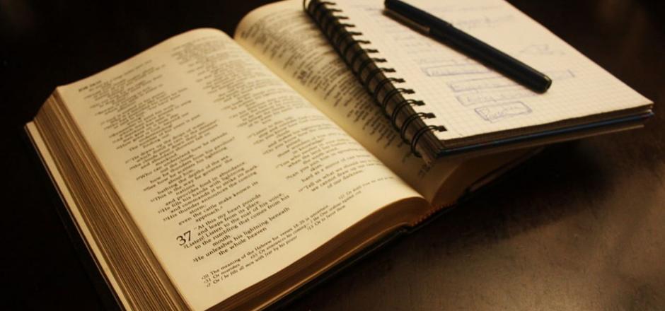diccionario abierto con libreta y lápiz encima